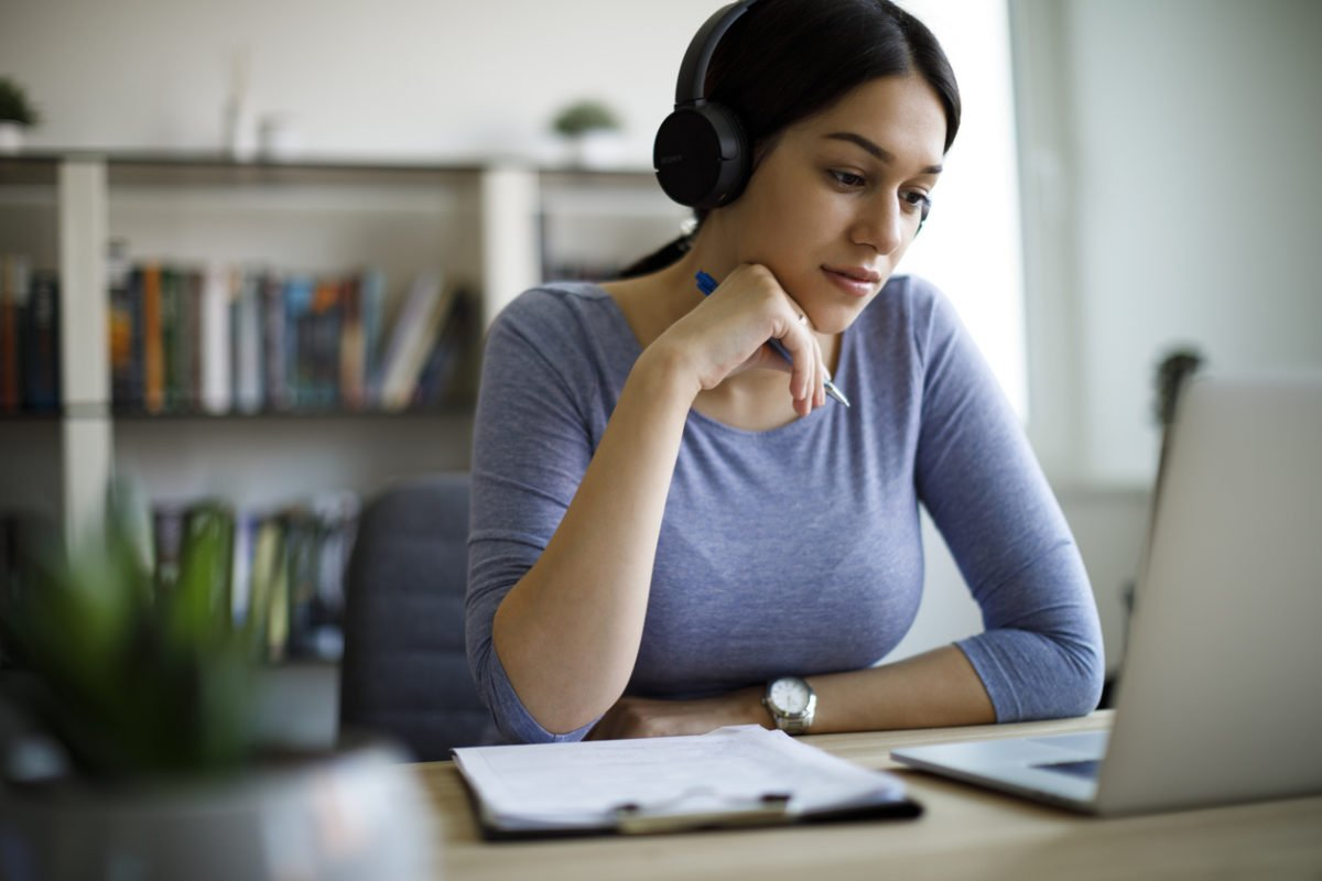 young woman wearing headphones working on laptop remotely from home as a digital court reporter and transcriptionist